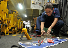 Houston native/Sailor uses a flow divider while fixing a forklift battery charging station in the hangar bay of USS Ronald Reagan