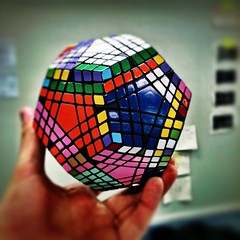 rubik's cube(0.0), glass(0.0), puzzle(1.0), hand(1.0), mechanical puzzle(1.0), toy(1.0),