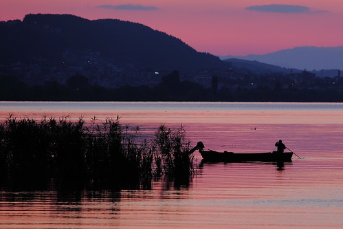city sunset sky mountain lake man color reflection water silhouette horizontal clouds reeds outdoors person one boat fishing fisherman greece oar ioannina epirus ελλάδα pamvotis ιωάννινα παμβώτιδα