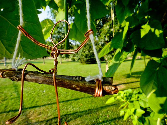 Get into the swing of Winnemac Park (wire figure on catalpa tree)