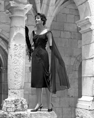 Model posing in ruins, wearing a sleek black knee-length gown and a sheer cape, with high heels.