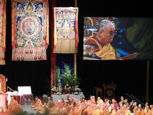 Buddhist nuns assembled on one side of the stage for the first time, over which His Holiness the 14th Dalai Lama's video appears, shrine, Kalachakra mandala and White Arya Tara brocade thangkas, Kalachakra for World Peace, Washington D.C., USA