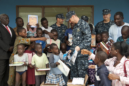 Sailor hands out school books to children in Nigeria.