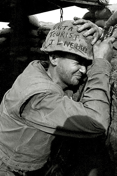 Clutching helmet and weapon, a Marine winces as North Vietnamese mortar rounds fly overhead during enemy shelling, Khe Sanh, South Vietnam, by Paul Stephanus