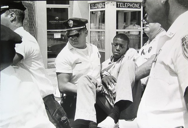 Eddie Brown calmly being carried off by the Albany police, 1963, by Danny Lyon