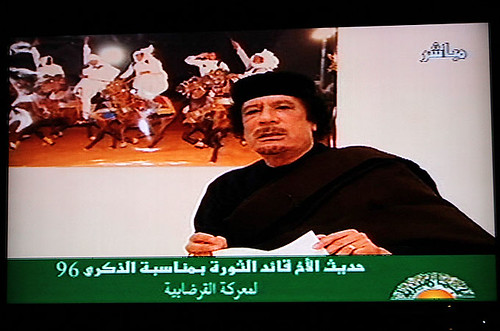 Poster Libyan revolutionary leader Muammar Gaddafi speaking on television in the North African oil-rich state. Libya fought off an imperialist onslaught for nearly a year and is now under neo-colonial chaotic rule. by Pan-African News Wire File Photos