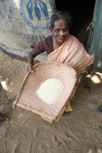 An Older Lady Cleaning Rice Outside Of Her Home Constructed From Unhcr -8842