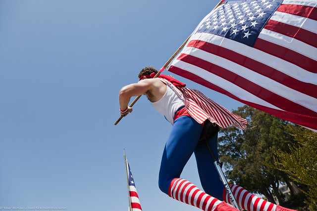 Young man on unicycle with American flag. People at Morro Bay, CA Fourth of July 2011 Celebration