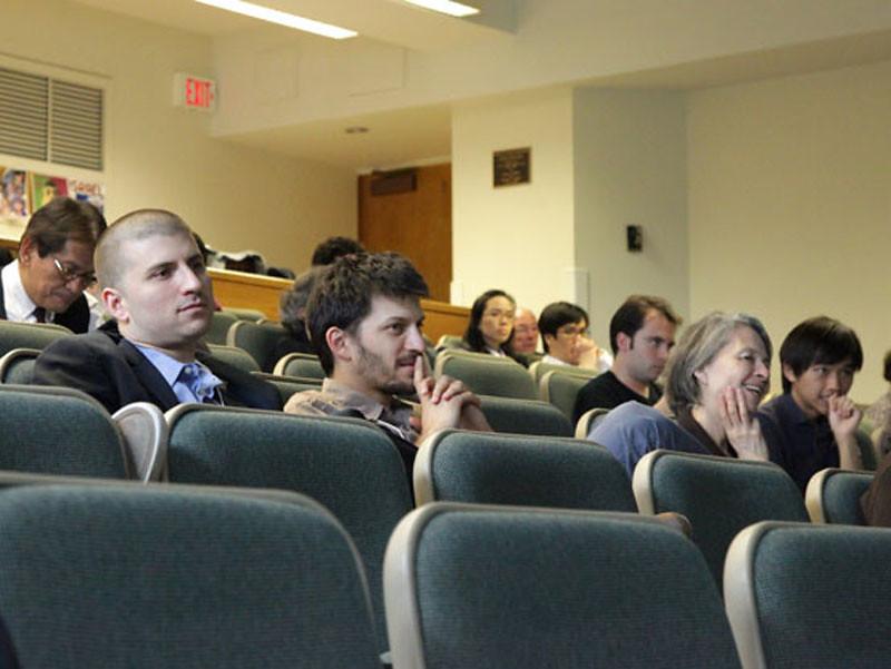 Walter Isard's grandsons,Thomas and Nick Yogada, and daughter, Toni Isard Yogada, react to presentations.
