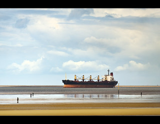 Big ship sails into the river Mersey watched over by the Ironmen of Crosby