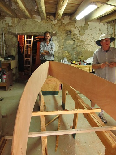 Fitting spreaders to keep the boat the right width.  It is upside down at the moment.  Plywood canoes being built in France using duct tape.