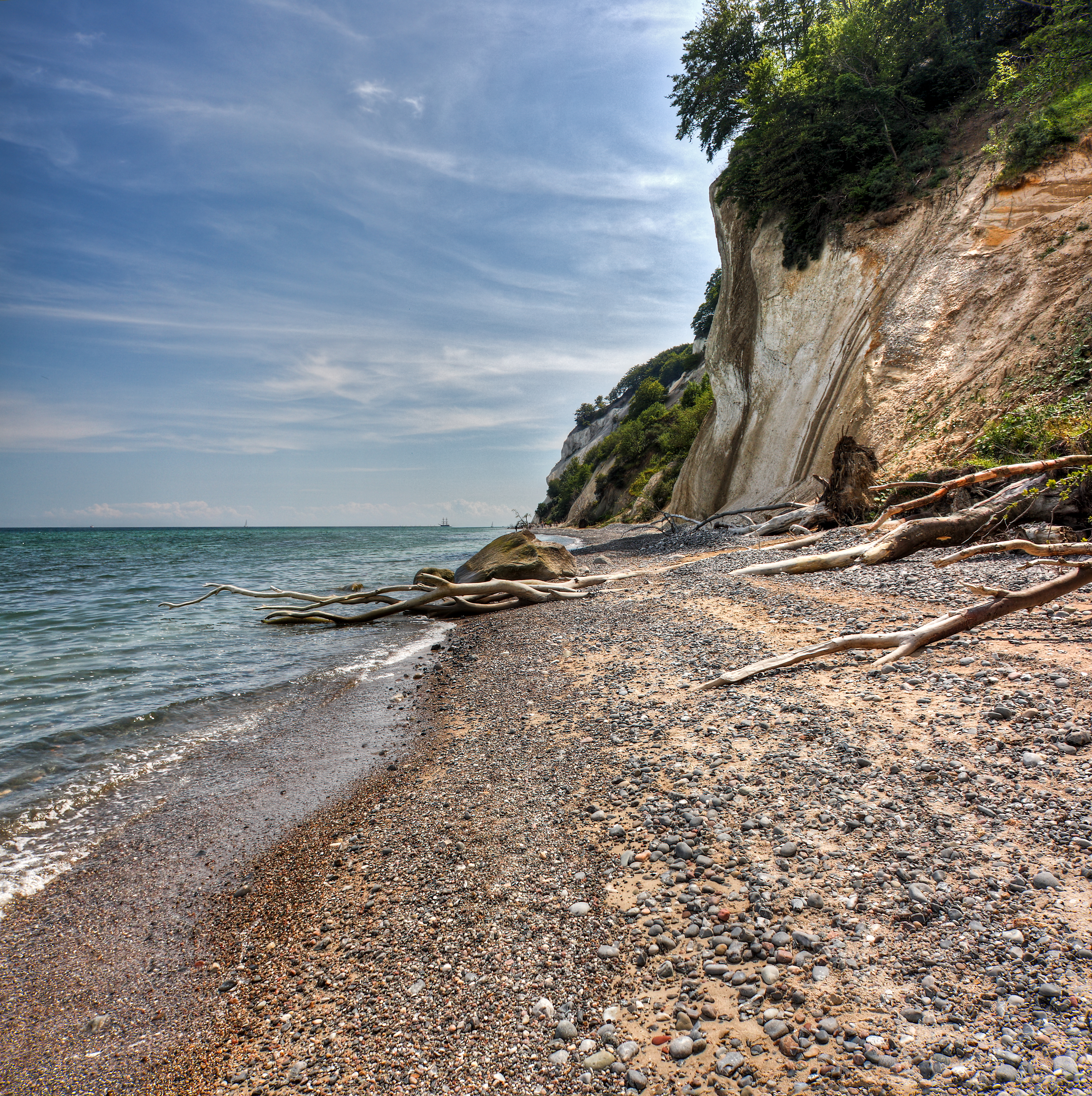 Image is made ​​of 2 widescreen images overlaid on each other (panorama), ie 2x 3 Exposure to AEB of + -1.5 (hdr)  Møns Klint, English: the Cliffs of Møn. The chalk forming the cliffs consists of the remains of shells from millions of microscopic creatures (coccolithophores) which lived on the seabed over 70 million years ago. As a result of huge pressure from glaciers moving west, the terrain was compacted and pushed upwards, forming a number of hills and folds. When the ice melted at the end of the last ice age about 11,000 years ago, the cliffs emerged. They form part of the same deposits as the cliffs of Rügen, Germany, on the other side of the Baltic. Today, it is possible to find fossils of various types of shellfish as the sea continues to erode the chalk. Erosion also caused one of the highest points on the cliffs, the Sommerspir, to fall into the sea in 1998, and in January 2007, there was an even larger landslide around the Store Taler, in the northern part of the cliffs, creating a 300-m long peninsula of chalk and fallen trees stretching out into the sea below. source: en.wikipedia.org/wiki/M%C3%B8ns_Klint  All Rights Reserved © René Eriksen. Please do not use my pictures outside the Flickr, without my permission.