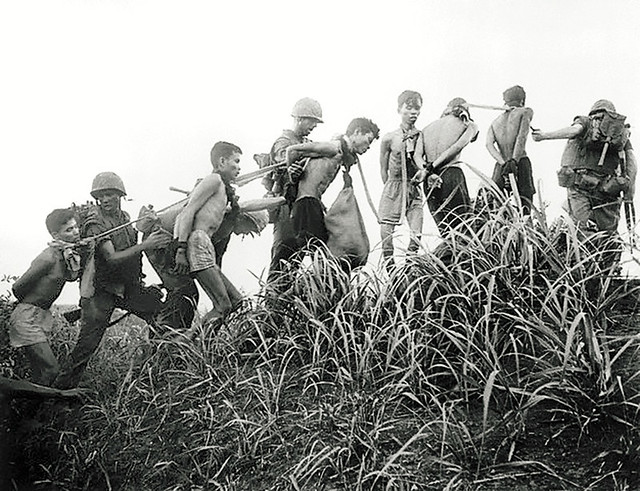 Viet Cong prisoners with their hands tied behind their backs are marched along in a small group where each man is joined to the other by cloth bands around the neck, Da Nang, South Vietnam, 1965, unattributed