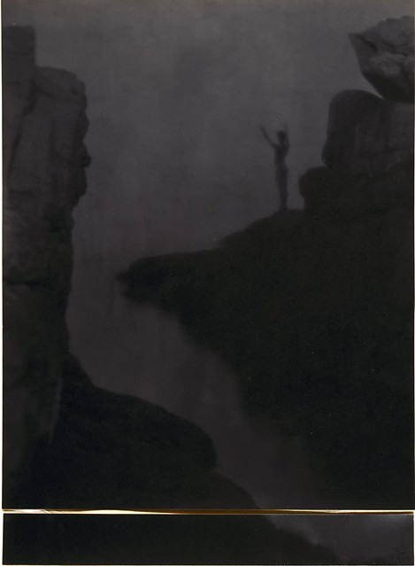 Boy in rocky landcape above water, arms raised, silhouette, by F. Holland Day 1905