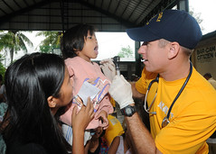 SUBIC, Philippines (July 28, 2011) Lt. Robert Hanson, assigned to the submarine tender USS Frank Cable (AS 40), performs a medical examination on a Filipino woman during a community service project.  (U.S. Navy photo by Mass Communication Specialist 1st Class Melvin Nobeza)