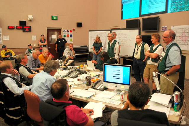 Environmental experts (standing) discuss Las Conchas Fire situation with senior emergency managers (seated).  Emergency Operations Center, Los Alamos National Laboratory.  Photo by Jeff Berger.