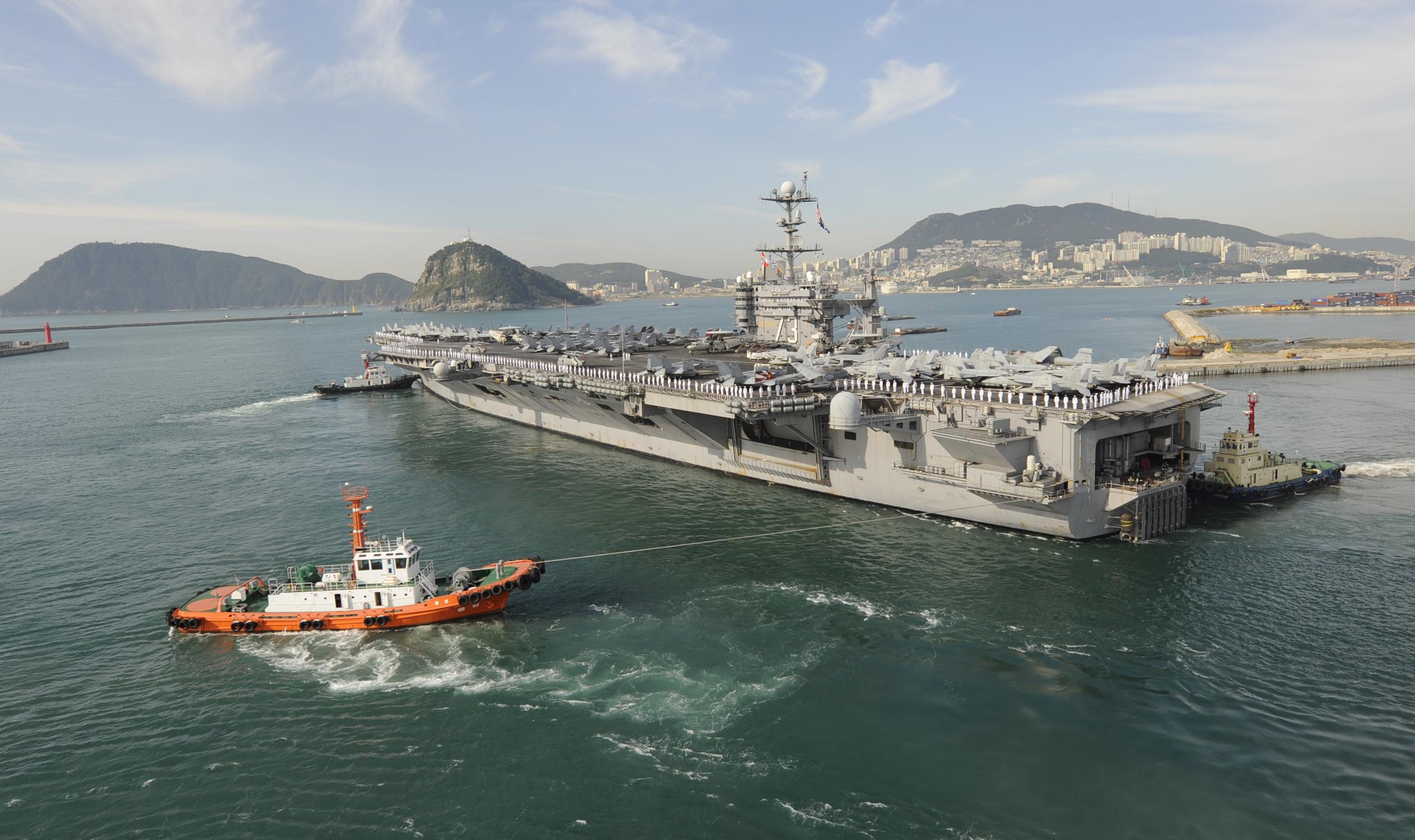 Tugboats assist the aircraft carrier uss george washington cvn 73