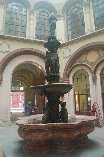 Der Brunnen steht unter einer Glaskuppel