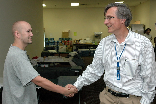 Brad Ferree (left) shakes hands with Charlie McMillan, director of Los Alamos National Laboratory, who visited employees who were evacuated from their homes in Los Alamos.  Photo by Kevin Roark