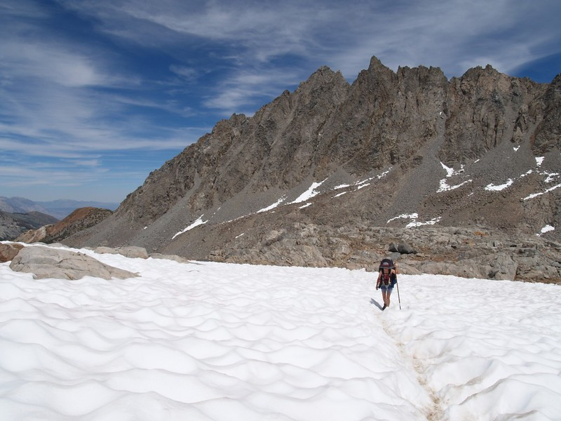 Vicki hiking across snow toward Bishop Pass with Picture Puzzle in the background