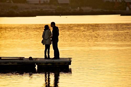 Couple on Pier on Shoreline Lake at Dusk