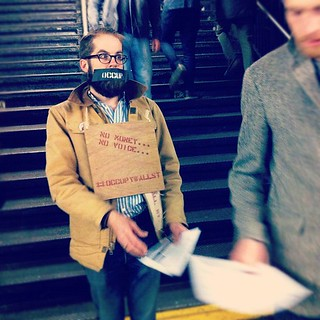 #OWS activist with a gag and placard handing out flyers at the Bedford Ave L station.