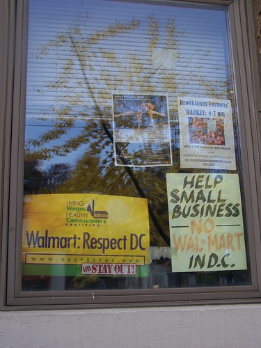 signs in a store window against Walmart's entry into Washington, DC, Brookland neighborhood
