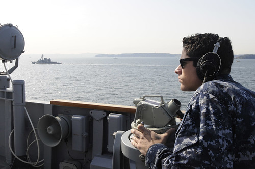 Quartermaster 2nd Class Louis Gonzales uses a telescopic alidade on USS Blue Ridge.