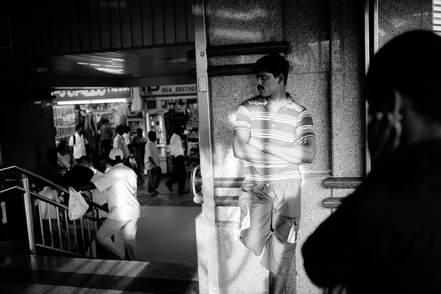 Basking in the light - this migrant worker was waiting at the MRT entrance for his friends to join him at Little India.