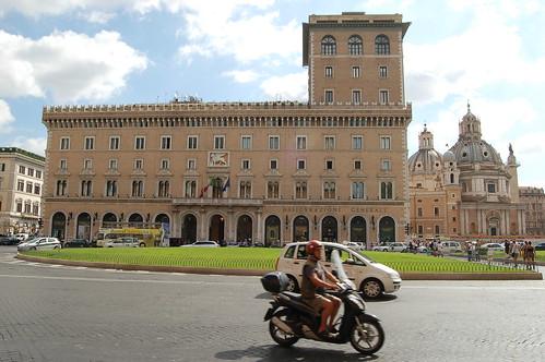 Der Palazzo Generali an der Piazza Venezia mit Vespa im Vordergrund