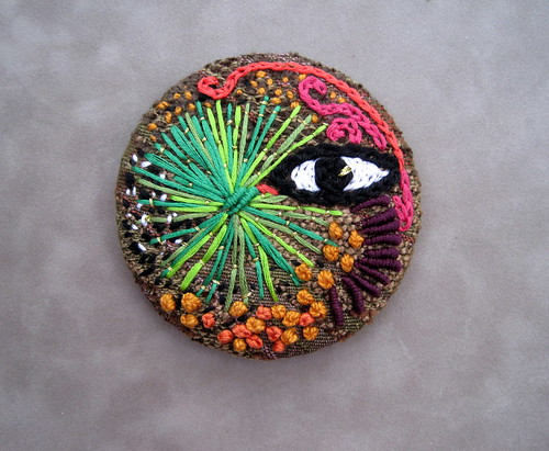 Freeform embroidery over a metal pinback button