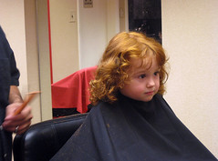 Speck with red curls and serious expression, in haircut apron