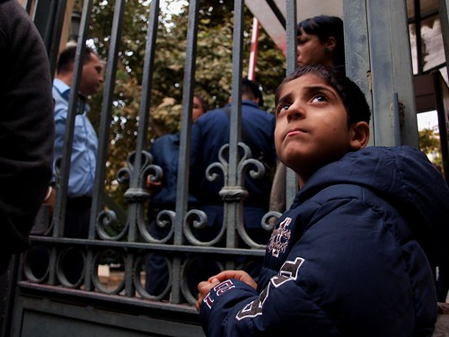 Seeing refugee families approach Greek riot police close gates to ministry building