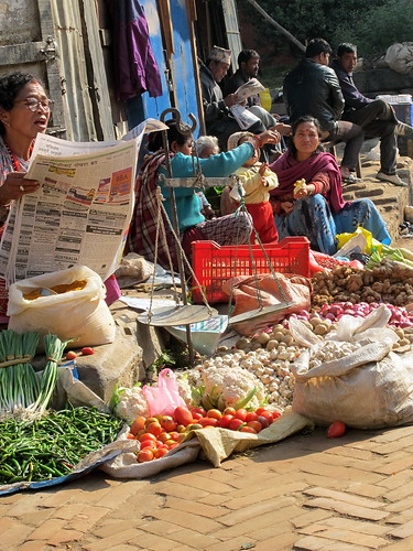 Lady reading the newspaper with her vegetables for sale