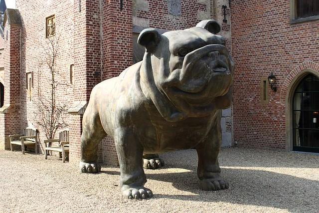 big statue of dog at entrance castle