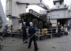 WHITE BEACH NAVAL FACILITY, Okinawa (Nov. 18, 2011) Sailors assigned to USS Tortuga (LSD 46) utilize one of the ship's cranes to load a medium tactical vehicle replacement assigned to Combat Logistics Regiment 3 into the well deck. (U.S. Navy photo by Mass Communication Specialist 2nd Class Casey H. Kyhl)