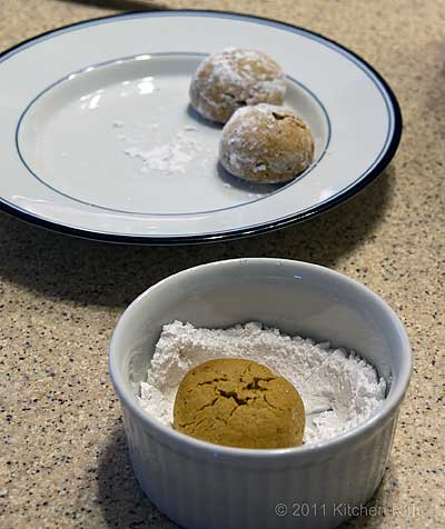 Rolling baked Pfeffernusse cookie in powdered sugar