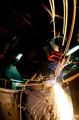 A Sailor operates a plasma cutter.