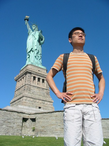 John standing before the Statue of Liberty in New York City