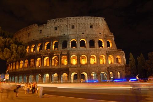 Vor dem Kolosseum wird eine Gruppe von Touristen fotographiert, autos fahren vorbei