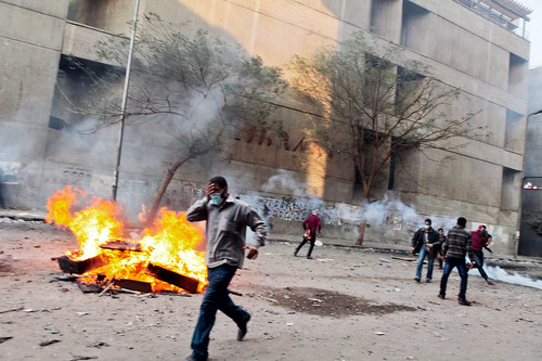 Egyptian masses flee amid the launching of teargas cannister designed to clear people out of Tahrir Square. The people are demanding an end to military rule of the North African state. by Pan-African News Wire File Photos