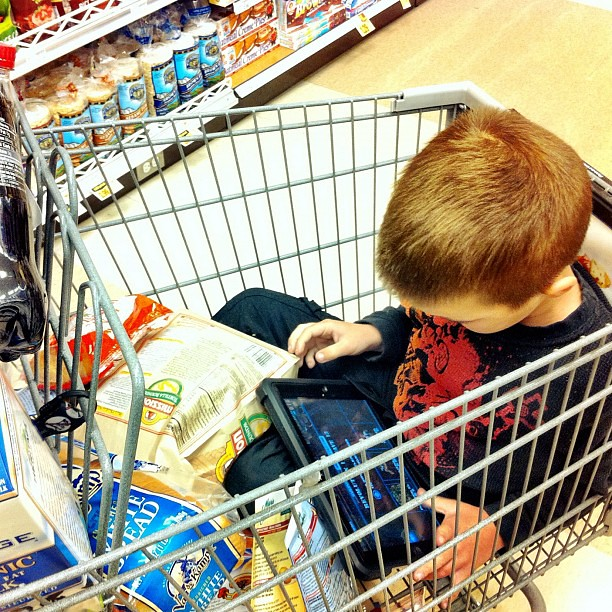 He is too involved in his game to realize that the groceries are piled on top of him.