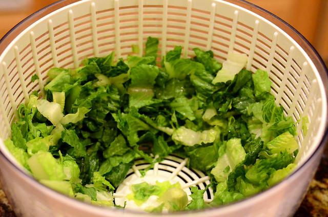 Chopped Romaine lettuce leaves inside a salad spinner.