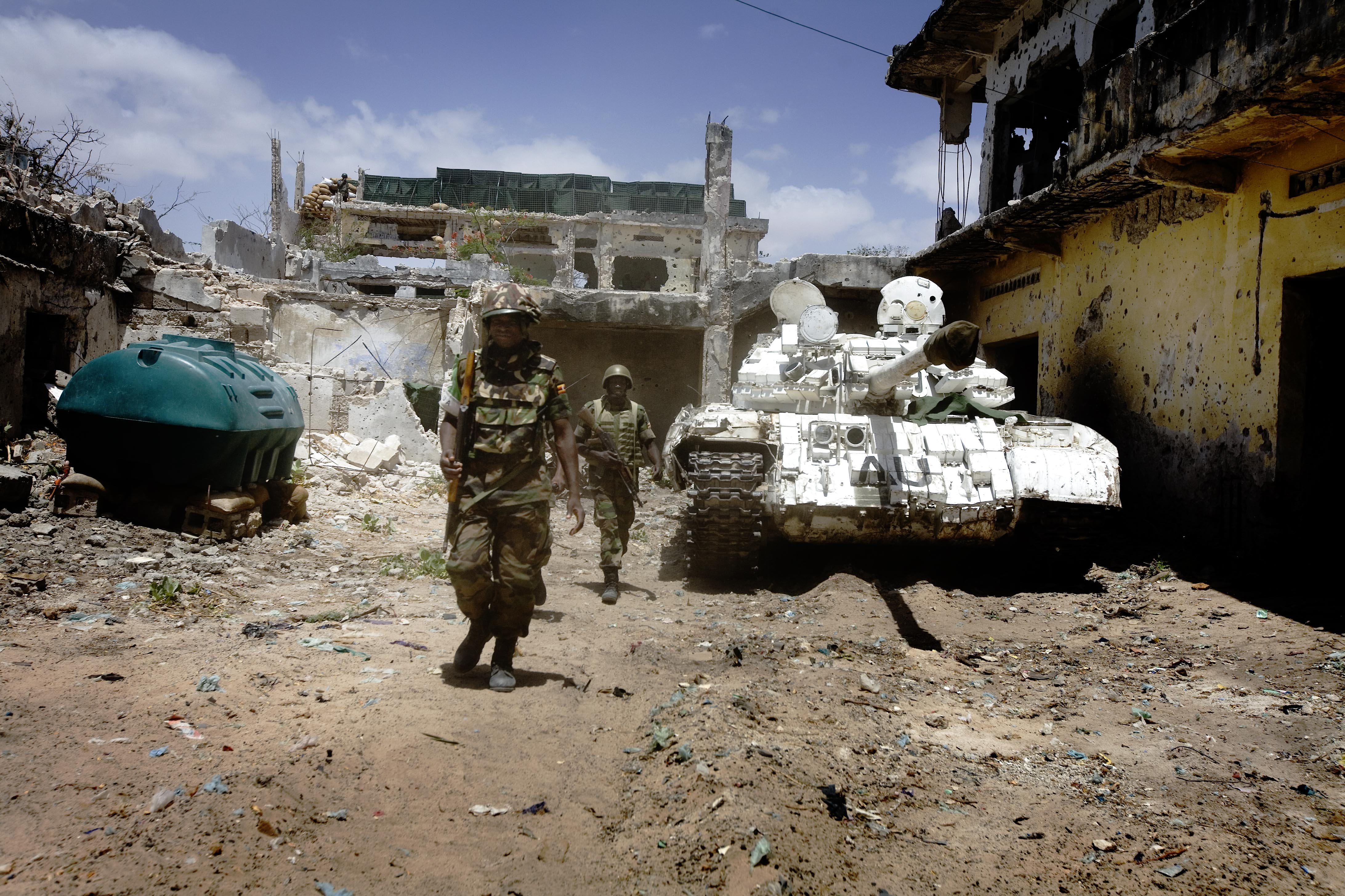 AU soldiers walk passed an AU tank in a house they have just taken from the control of Al Shabaab insurgents in Mogadishu, Somalia