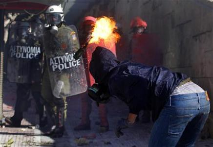 Greek youth tosses petrol bomb at riot police amid general strikes and rebellions in the European country. The Greek government has been forced by the banks to impose austerity on the workers. by Pan-African News Wire File Photos