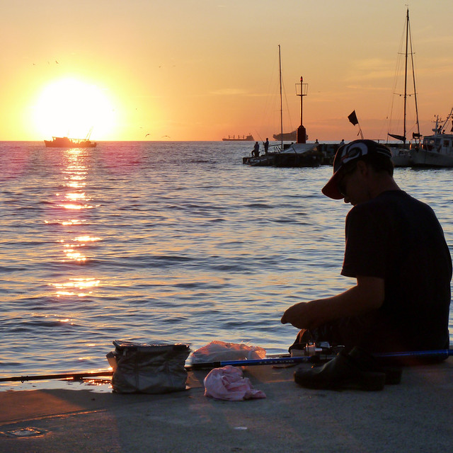 Young man preparing bait for good sunset fishing