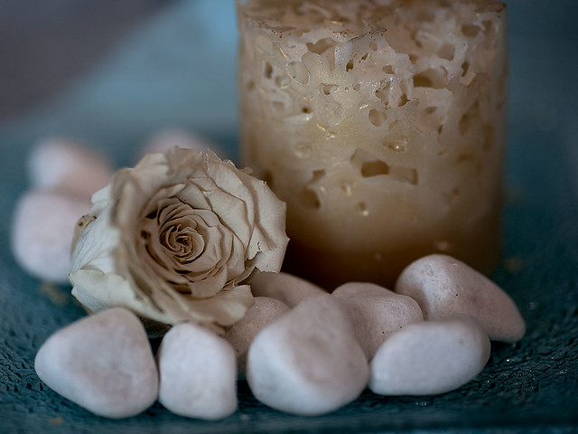 White rose, candle and stones