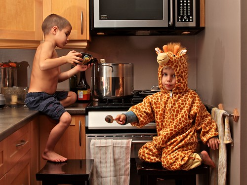 Two children cooking a meal together in the kitchen.
