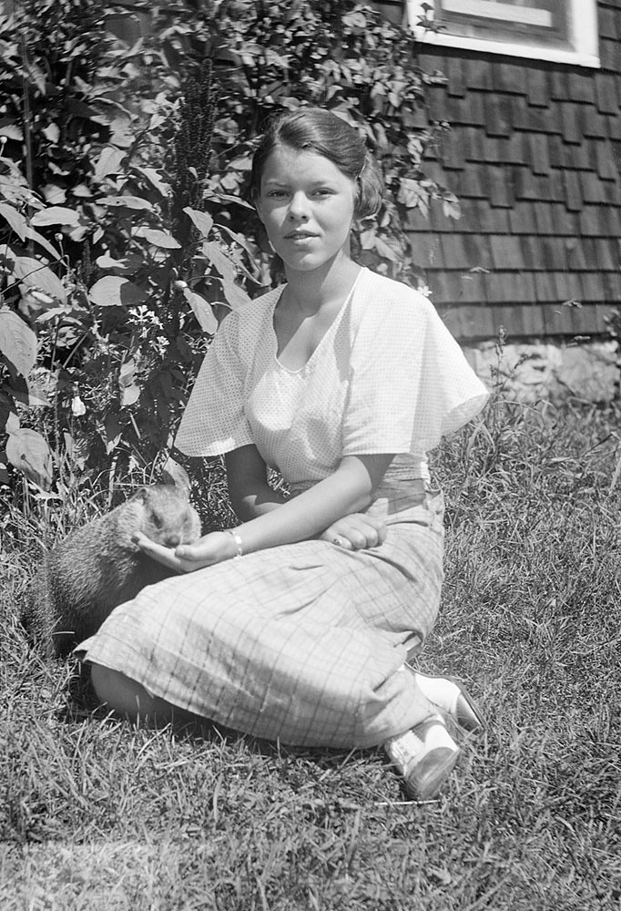 My Grandma back around 1934 with the family pet woodchuck. Moe's River, Quebec. Canada.