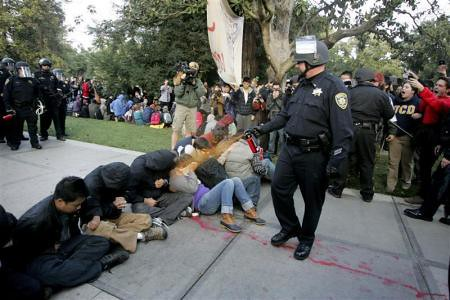 Cops spraying pepper chemicals into the faces of students at the University of California at Davis. The acts of police brutality have been condemned throughout the country. by Pan-African News Wire File Photos